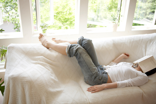 Woman sleeping on sofa in living room, book covering face